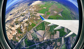 View from airplane window on fields and mountains Stock Photos