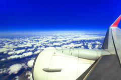 The view from airplane window during flight over clouds with blue sky Royalty Free Stock Photo