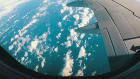 View from the Airplane Window on a Landscape of Clouds. Clouds are seen through the window of a jet airplane. Airplane flies above the weather stock footage