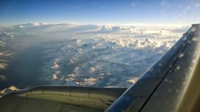 View from airplane window of mountains with snow on the top, clouds, wing and blue sky. For travel concept Stock Images