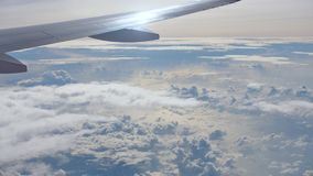 View from the airplane window with part of the wing and the beautiful clouds. View from the airplane window with part of the wing and the beautiful clouds stock video footage