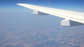 View through airplane window - plane wing moving above fields stock footage