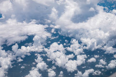 View from airplane window showing blue sky and white clouds Stock Image