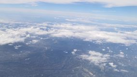 View from airplane window showing houses, buildings, clouds, mountains, skyline, ocean, ships and big boats stock video