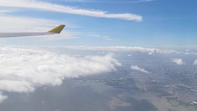 View from the airplane window showing skyline, clouds, beautiful forest, ocean, ships, mountains, islands, houses and buildings stock video