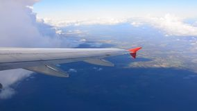 The view from an airplane window on sky with cloud. Aircraft makes the climb with a turn through the clouds. The view from an airplane window stock video footage