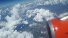 View from the airplane window to the blue sky and white clouds, an orange turbine on the wing of the plane, a view of. The earth from the sky through the clouds stock video footage