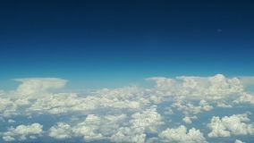 View from the airplane window to the blue sky and white clouds on a sunny day, lots of white clouds float above the. Earth, a view of the earth through white stock video footage