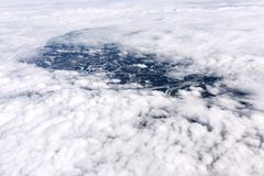 A view from the airplane window to clouds and earth. Stock Photo