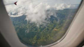 View through an airplane window on the tropical island, ocean, sea, sky and clouds. Aerial view sea, clouds and sky as. Seen through window of an aircraft stock video footage