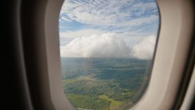 View through an airplane window on the tropical island, ocean, sea, sky and clouds. Aerial view sea, clouds and sky as. Seen through window of an aircraft stock video