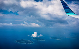 View from airplane window trough clouds at tropical island. View from airplane window trough the clouds at tropical island archipelago stock images