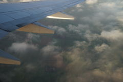 View from airplane. Wing with clouds. View from airplane. Clouds with green land at background Stock Images