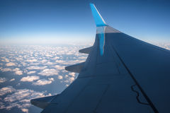 View at the airplane wing over curly clouds with blue sky Stock Images