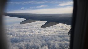 View of airplane wing through plane window. Flying above the clouds. stock footage