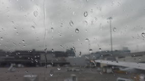 View of airport through airplane window on a rainy day stock video