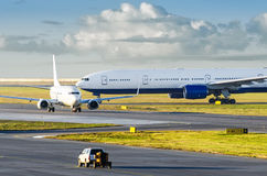 View at the airport with a large aircraft landed, and a small plane departing taxiing for takeoff. Stock Photo