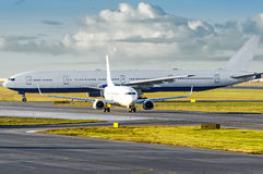 View at the airport with a large aircraft landed, and a small plane departing taxiing for takeoff. Stock Photos