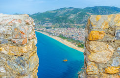 The view from Alanya castle. The view on Kleopatra beach, modern city and green Cilician mountains through the hole between the old battlements of Alanya castle Royalty Free Stock Images