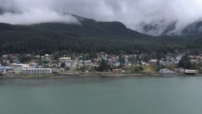 View of Alaskan Coastline and small town from passing cruise ship. A view of a small Alaskan coastline town from a passing cruise ship stock footage