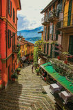 View of alley in hillside, buildings with bindweed and Lake Como in Bellagio. Stock Photography