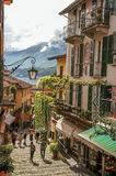 View of alley in hillside, buildings with bindweed and Lake Como in Bellagio. Royalty Free Stock Images