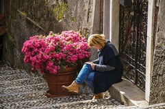 View of alley in hillside with woman reading in front of a gate in Bellagio. stock photo
