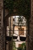 View of an alley in Spello town Umbria, Italy with some old copper pots hanging on the rooftop of an arch. View of an alley in Spello town Umbria, Italy, with Royalty Free Stock Images