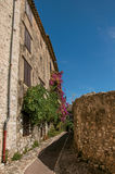 View of alley with stone houses on a blue sunny day in Saint-Paul-de-Vence. Royalty Free Stock Image