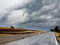 View along country road. With concrete barrier on the left and storm clouds overhead stock photos