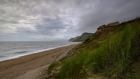 View along the Dorset coast from the beach near Eype on a windy day with long exposure smoothing the sea and blurring the ferns, stock image