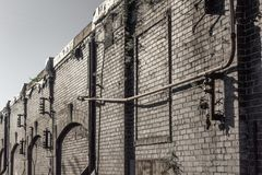 View along the face of an industrial warehouse building, old brick and pipes. Horizontal aspect stock images