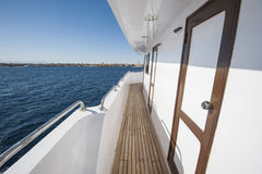 View along gangway of a large private motor yacht out at sea. View along gangway down side of a large private motor yacht under way sailing out on tropical sea Royalty Free Stock Photo