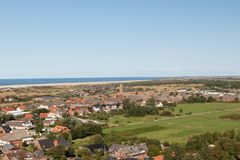 View along the grass area fields and the buildings and houses on the sea under a blue sky on the northern sea island borkum german. Y and photographed in multi royalty free stock photo