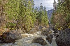 Merced River and Vernal Fall in Yosemite. A view along the Mist Trail next to the Merced River with the Vernal Fall in the distance Royalty Free Stock Images