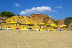 A view along Oura Praia Beach Albuferia with sun beds and sand royalty free stock photo