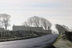 Countryside road on frosty winter morning. View along A588 road on a frosty winter morning with no vehicles on road and silhouettes of fence, trees and houses stock photography