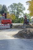 View along a road to diggers at a jobsite in a housing area. Dahlewitz, Germany - 10/15/2017 Stock Photography