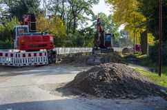 View along a road to diggers at a jobsite in a housing area. Dahlewitz, Germany - 10/15/2017 Stock Images