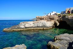 Rocky coastline and sea, Mellieha. View along the rocky coastline with a sea cave in the foreground, Mellieha, Malta, Europe Stock Image