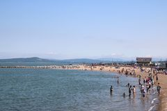 People on beach, sunny day, Morecambe, Lancashire. View along a sandy beach at high tide looking along the shoreline of Morecambe Bay, Morecambe, Lancashire royalty free stock photos