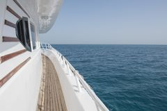 View along the side of a private motor yacht at sea. View along side walkway corridor of private moto yacht sailing on tropical sea ocean Stock Images