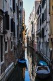 A narrow Venetian canal. A view along a still narrow canal in Venice, Italy Royalty Free Stock Photo