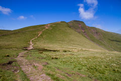 Pathway leading up to the summit of Pen y Fan in the Brecon Beacons National Park. The view along the trail leading down from the peak of Cribyn up to the summit Stock Photo