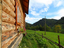 View along wall of the wooden house on mountain and meadow. Distance are seen wooded mountains and sky with clouds Stock Image