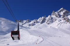 View on alpine downhill slope and lift cabine. A perspective view from the ski lift  on an alpine downhill slope with peaks and skiers Stock Photography