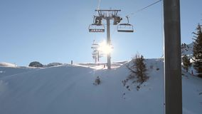View of an alpine mountain slope while traveling on chairlift stock video