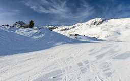 View of an alpine ski slope in mountains Royalty Free Stock Image