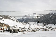 A view of an amazing beautiful village in the snow covered landscape and mountains and a cable car/lift in the alps switzerland in. Winter Royalty Free Stock Photography