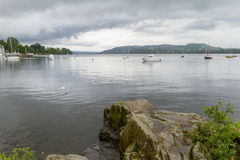 View from Ambleside lake shore of boats and flying sea-gulls. View from lake shore of boats and flying sea-gulls in Ambleside , Lake Windermere in the UK Stock Photos